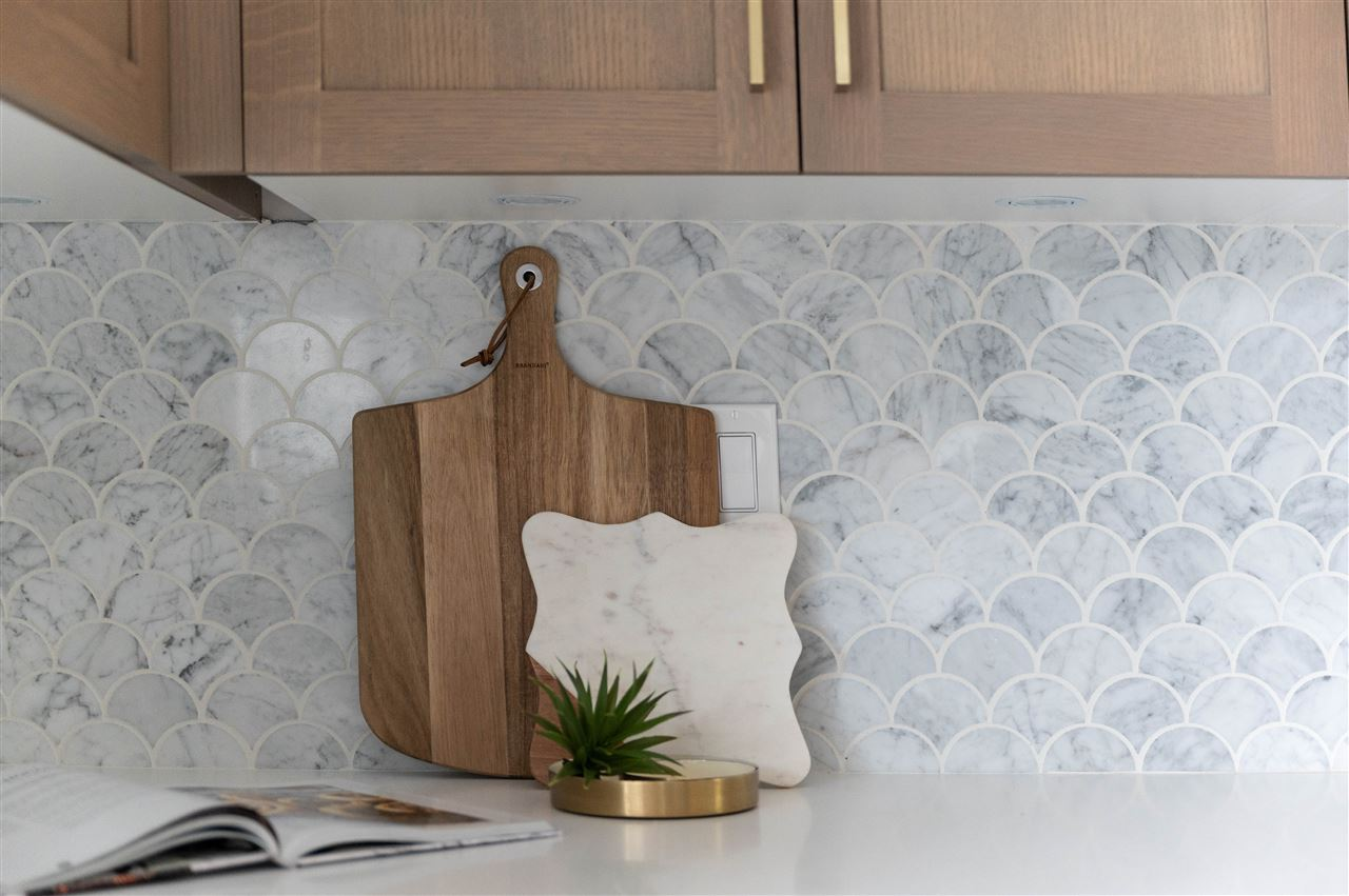 beautiful scalloped grey and white kitchen tile backslash