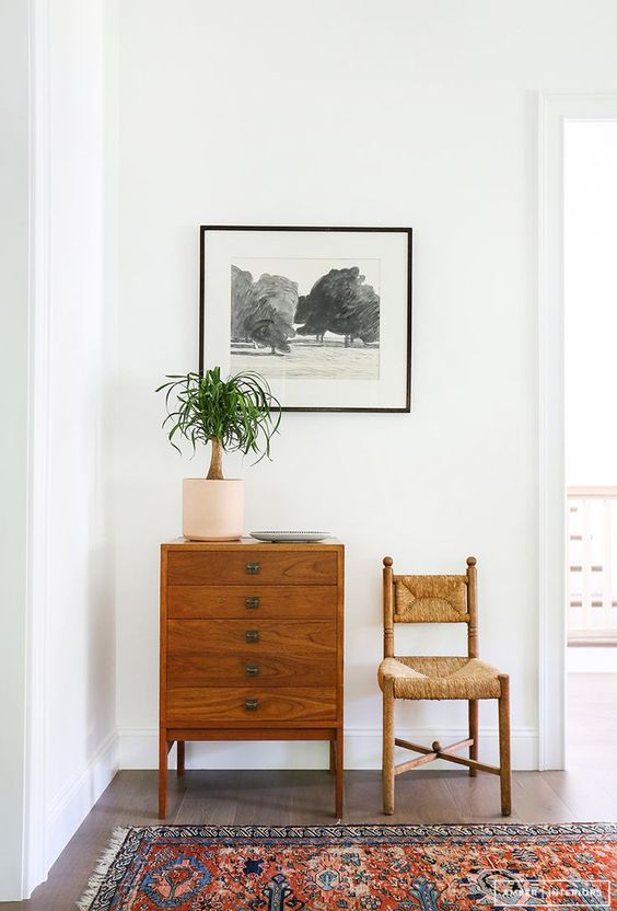 vintage rattan chair, dark brown entry way dresser with black and white artwork on wall.